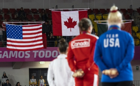 three athletes stand on the podium with the american and canadian flags in the distance
