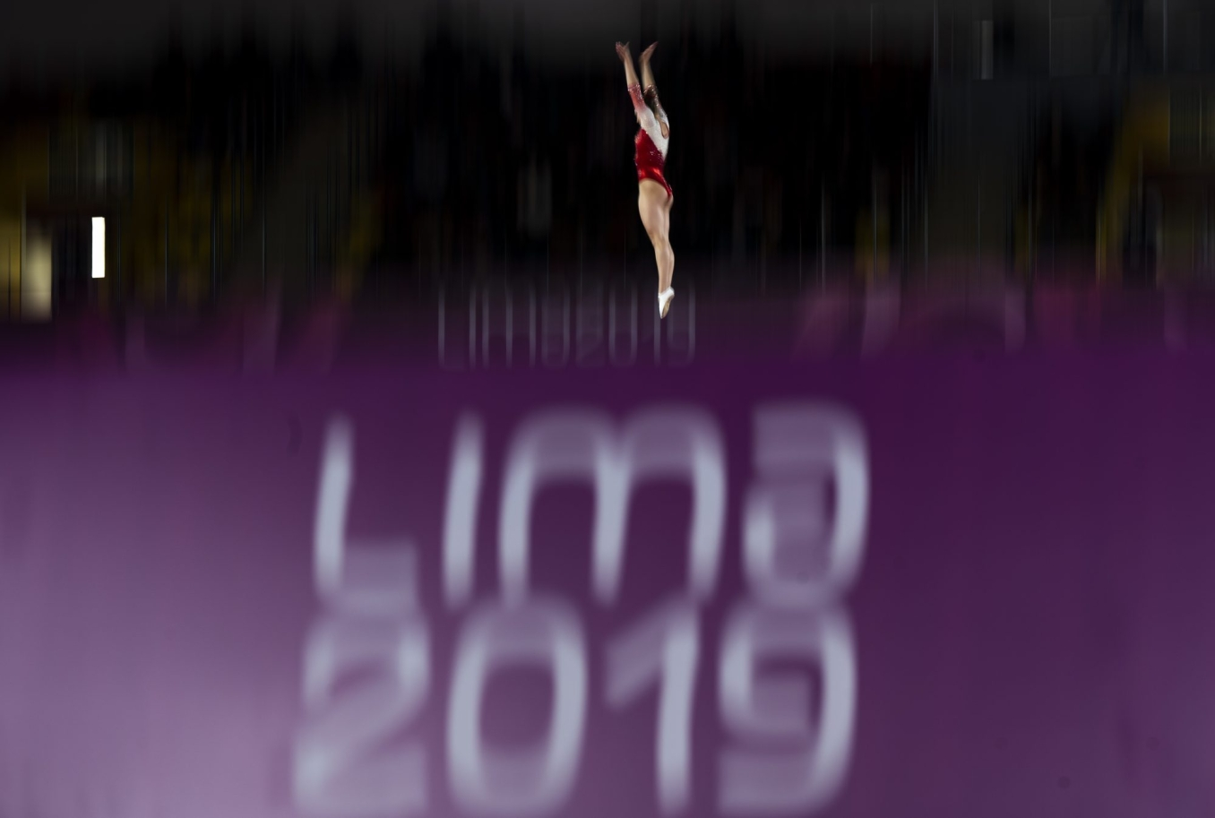 athlete in the air above a lima 2019 sign