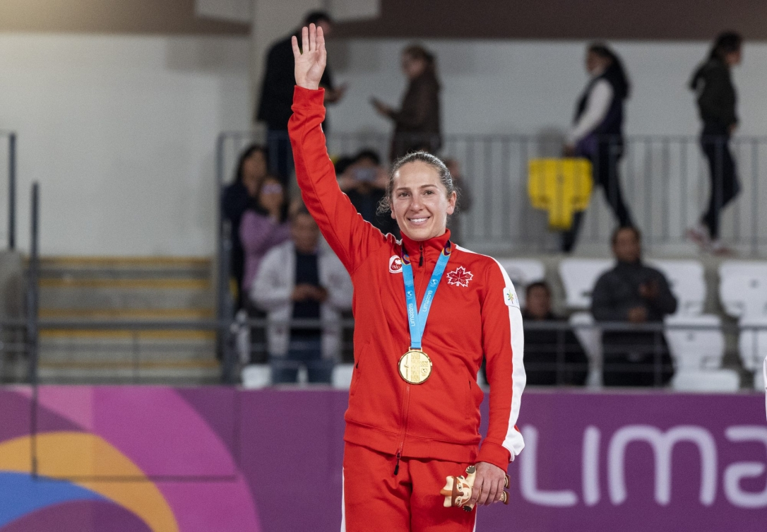 athlete raises her hand to acknowledge the crowd