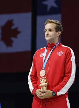 man stands on podium with a medal