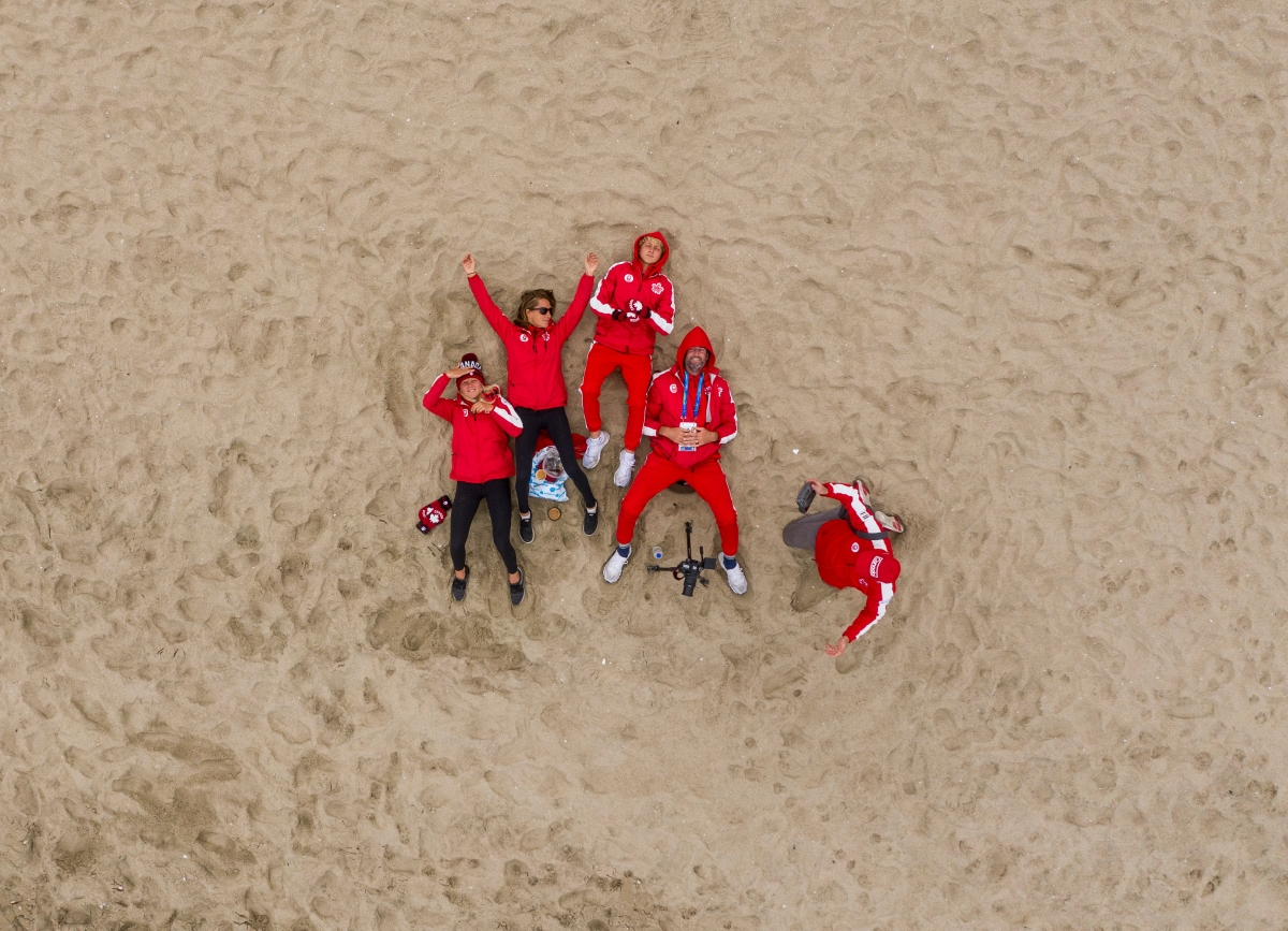 Surfers in their Team Canada Kits lay on the sand