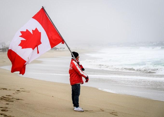 Team Canada coach holding a Canadian flag