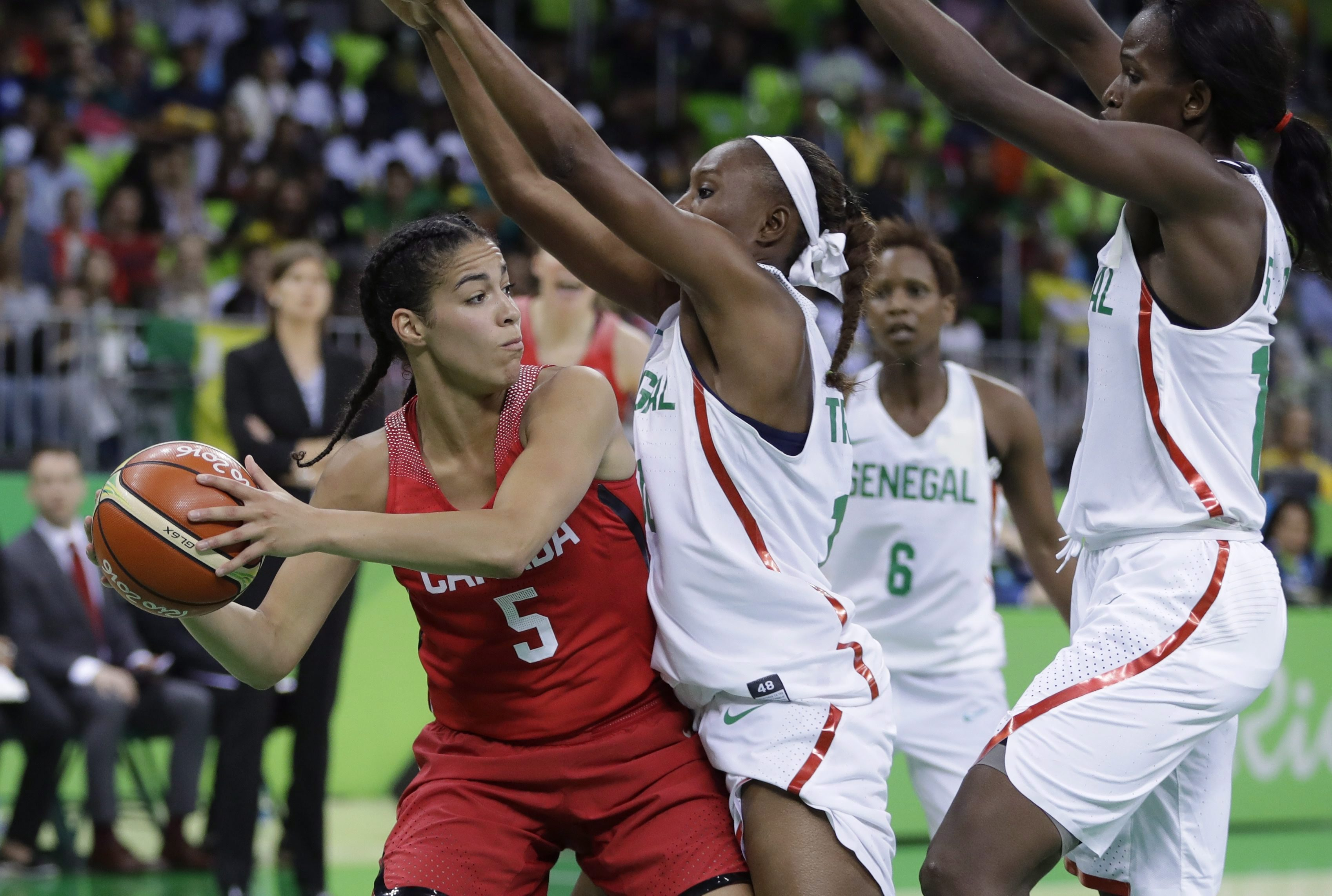 Kia Nurse holds the ball as she tries to get around two members of the Senegal team.