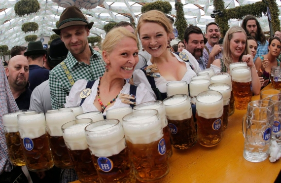Two Oktoberfest waitresses pose with a dozen beer steins