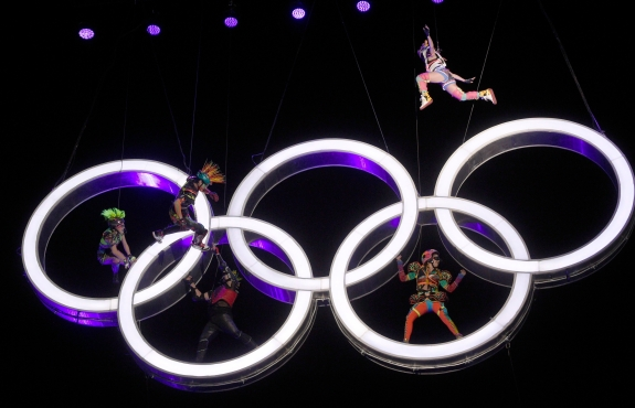 Actors perform alongside the Olympic rings which are up in the air