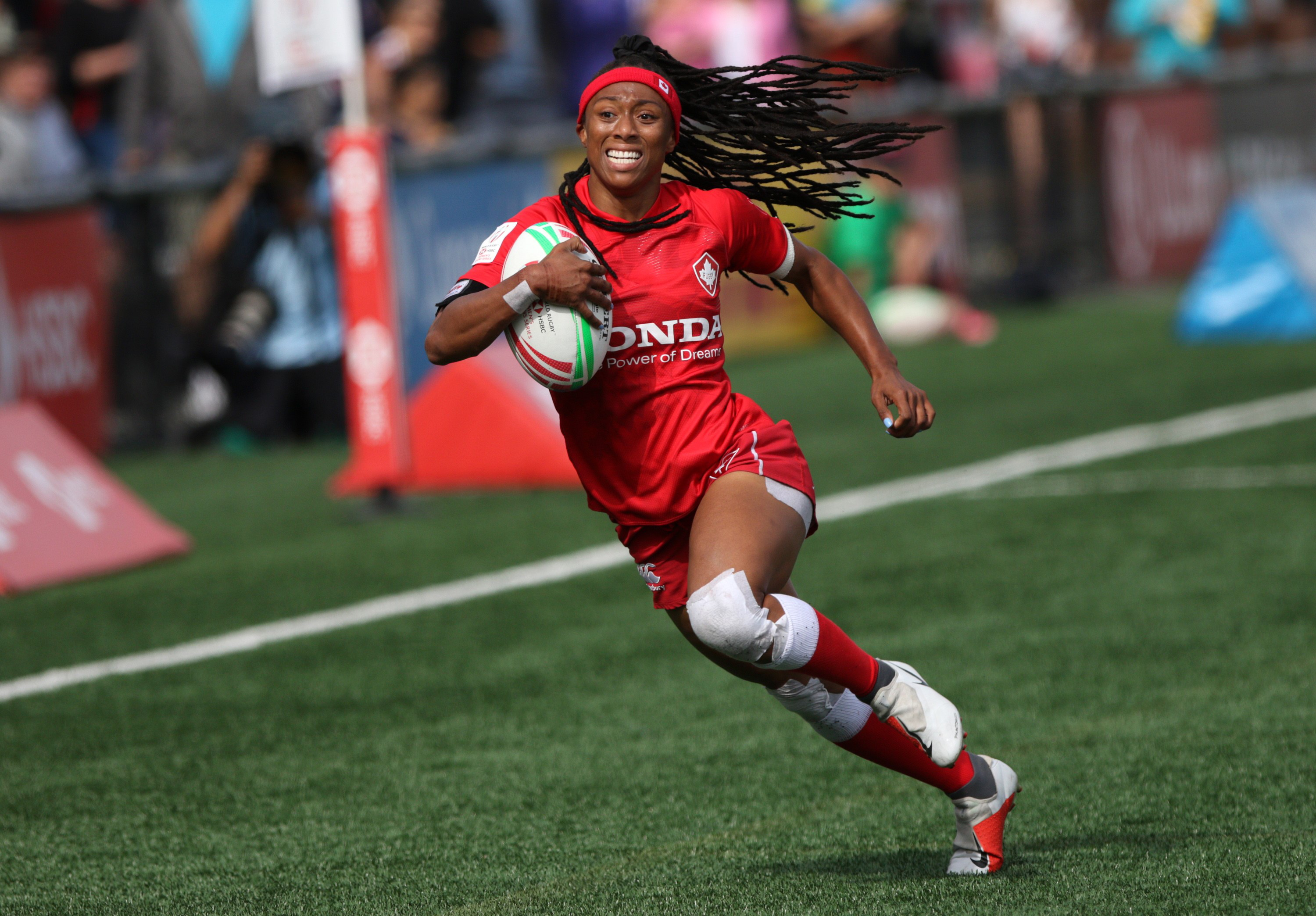 Charity Williams holds the rugby ball and runs.