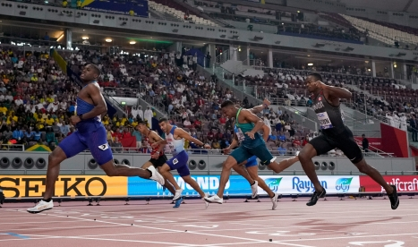 Christian Coleman, of the United States, crosses the line ahead of Aaron Brown, of Canada, and Adam Gemili, of Great Britain