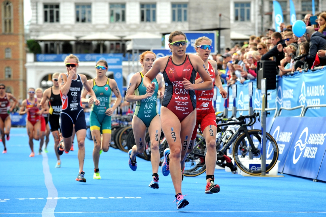 Female triathletes run past spectators (left) and a row of bikes (in front of spectators).