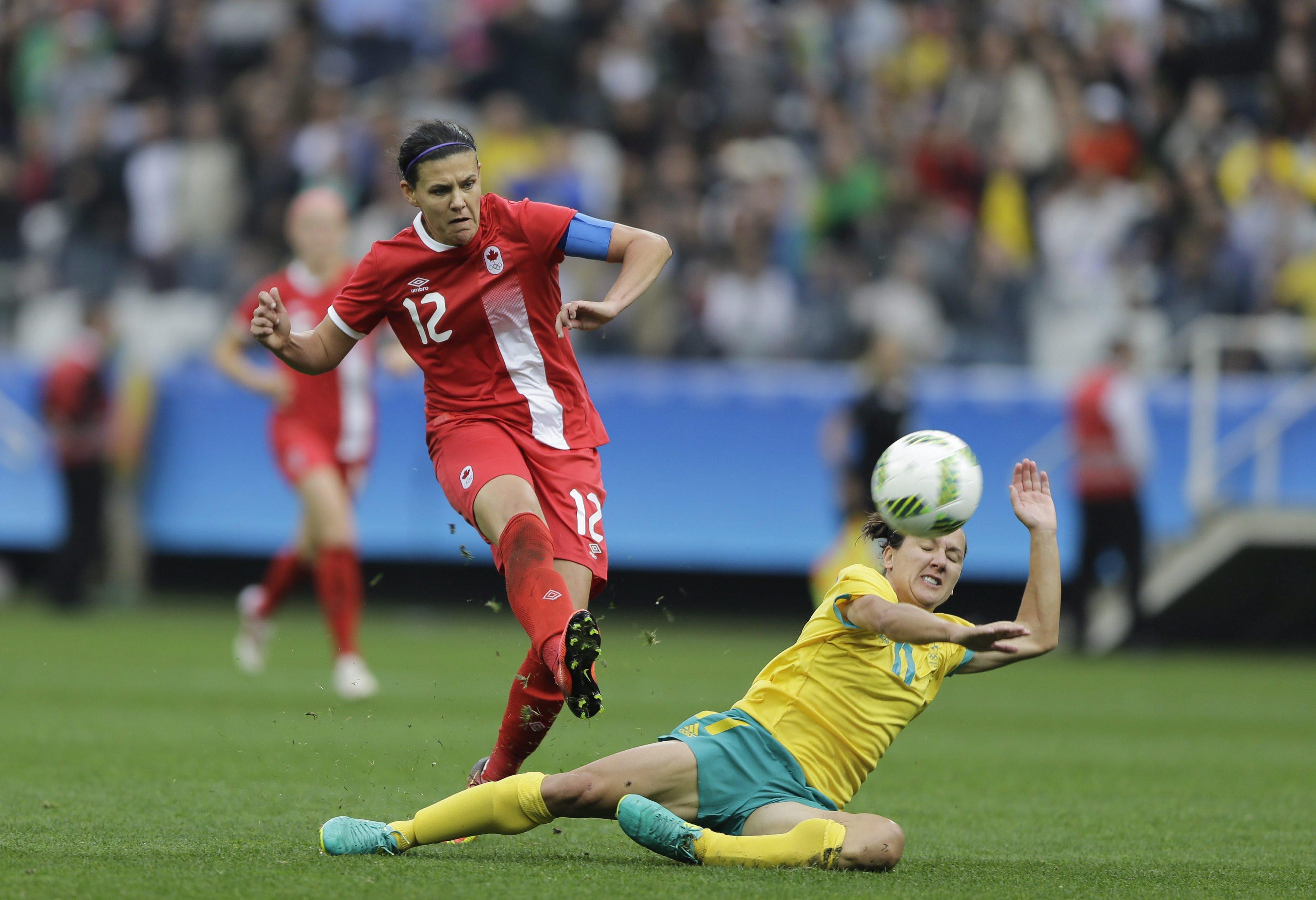 Christine Sinclair kicks the ball over a fallen Team Australian player.