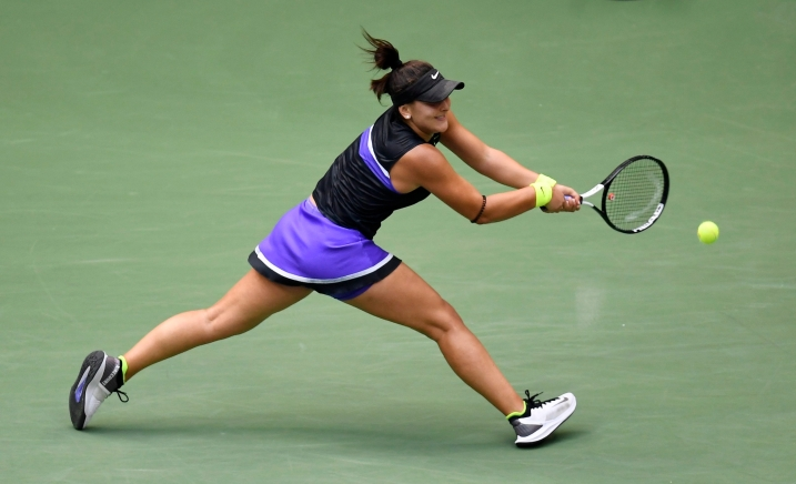 Bianca Andreescu returns a shot. She is wearing a purple and black outfit.