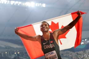 Andre de Grasse holds the Canadian flag over his head as he celebrates his silver medal in Doha.