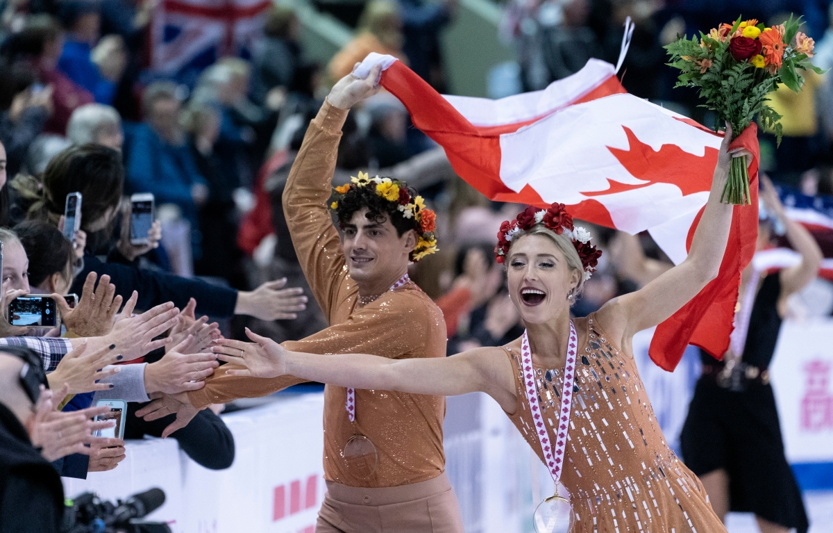 Piper Gilles and Paul Poirier reach out to the crowd during victory ceremonies at Skate Canada