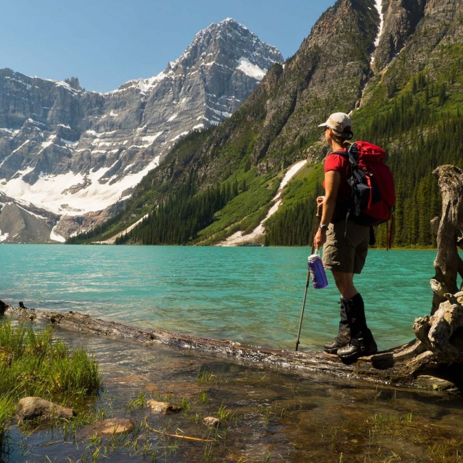 A hiker stands beside the turquoise water and looks out at the Mountains.