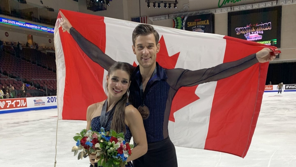 Laurence Fournier Beaudry (front) poses with Nikolaj Sørensen, who is holding the Canadian flag up behind him.