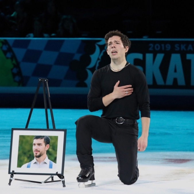 Keegan Messing kneels beside a picture of his late brother