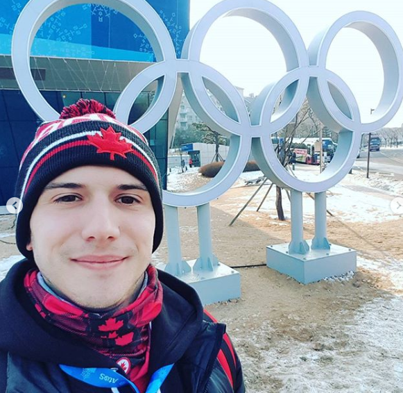Adam poses in front of the rings inPyeongChang