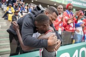 Marco Arop hugs his coach in the stands.