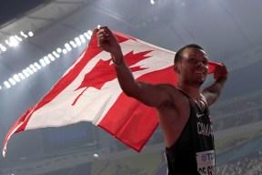 Andre de Grasse holding Canadian flag