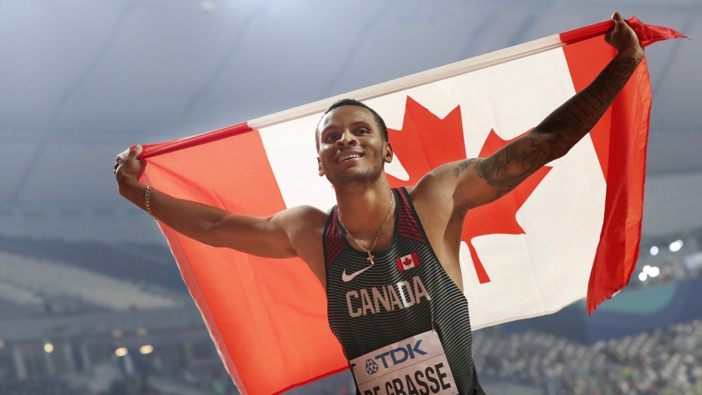 Andre De Grasse holds the Canadian flag up behind him.