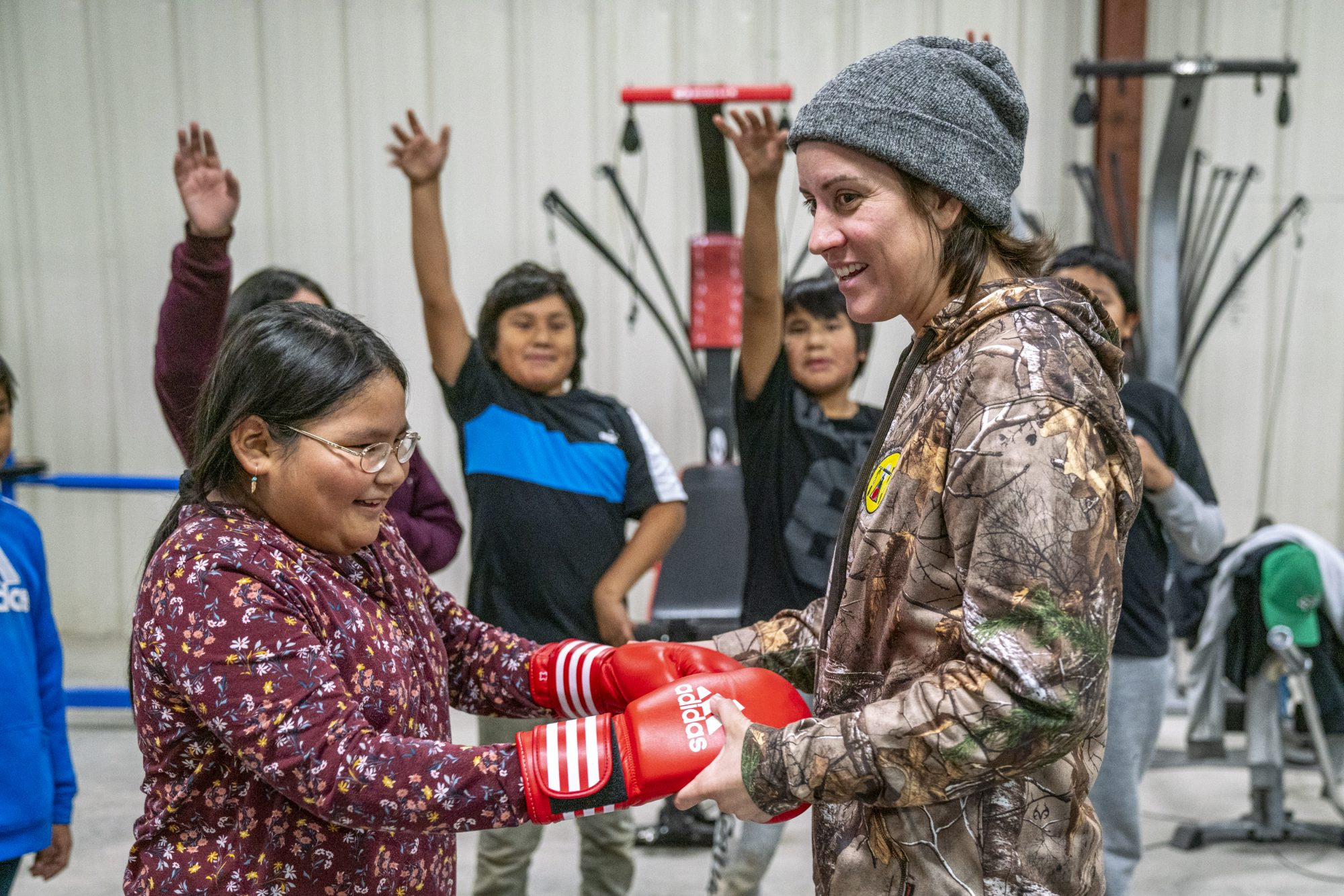 Mary Spencer shares her boxing gloves with a young student