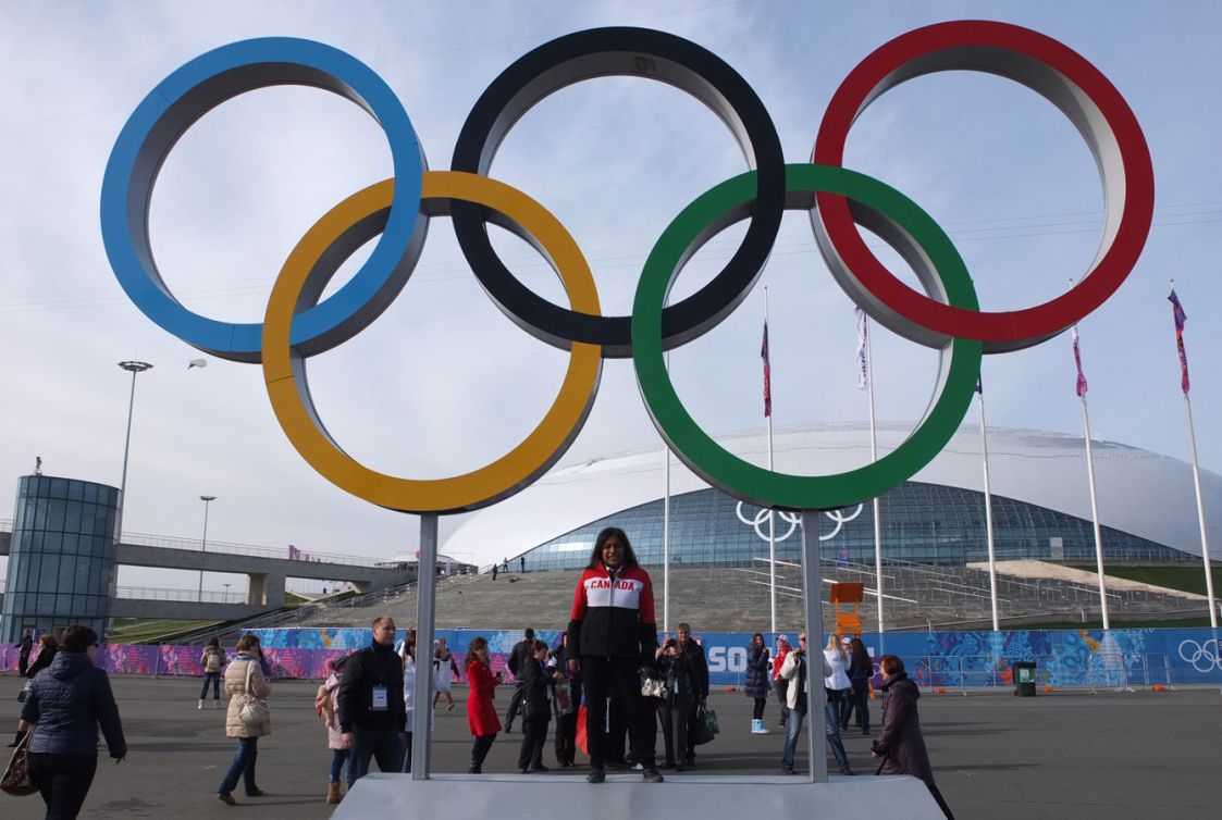 Team Canada volunteer Shanti poses in front of the Olympic Rings at the Sochi 2014 Olympic Park.