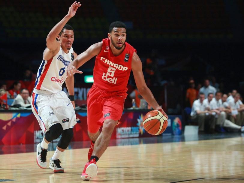 Canada's Cory Joseph, right, dribbles past Dominican Republic's Rigoberto Mendoza