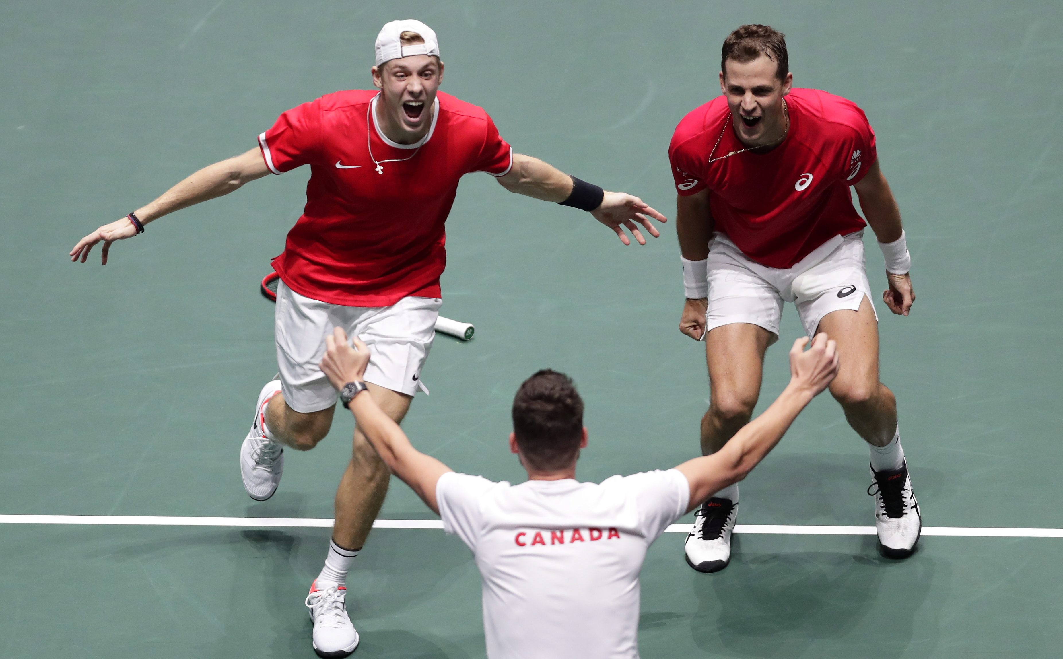 Denis (left) and Vasek run towards Frank (centre) after winning their semis match.