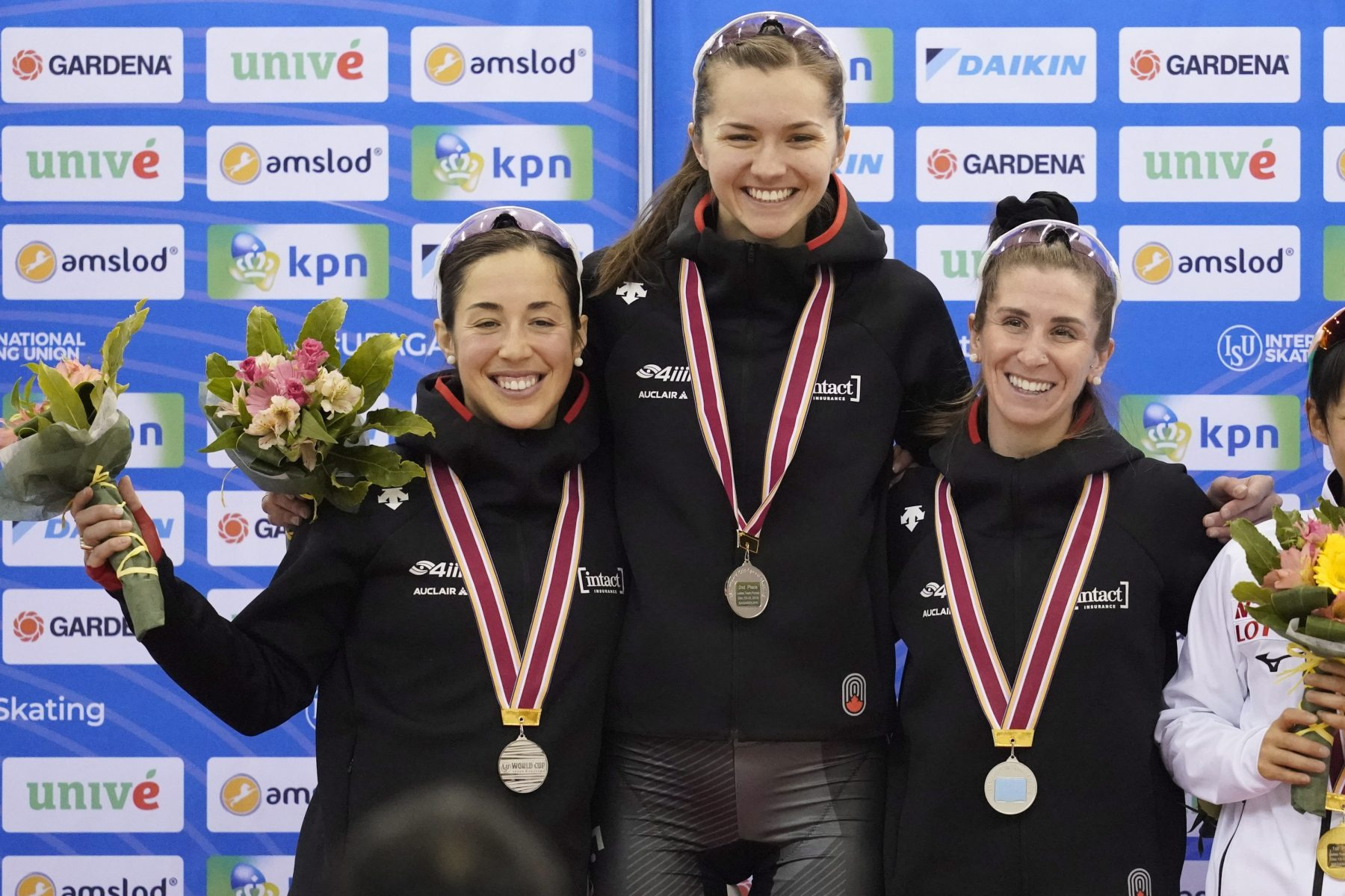 Second placed Canada team, Ivanie Blondin, Isabelle Weidemann and Valerie Maltais, celebrate on the podium during a medal ceremony for the ladies team pursuit race of the speed skating World Cup at the M-Wave in Nagano, Japan, Sunday, Dec. 15, 2019. (AP Photo/Toru Hanai)