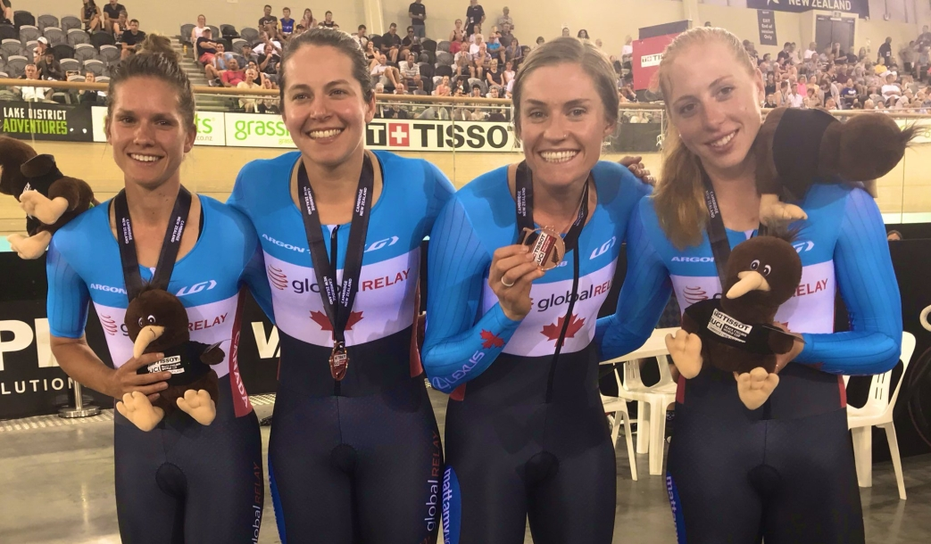 The women's team pursuit squad poses for a photo with their bronze medals.