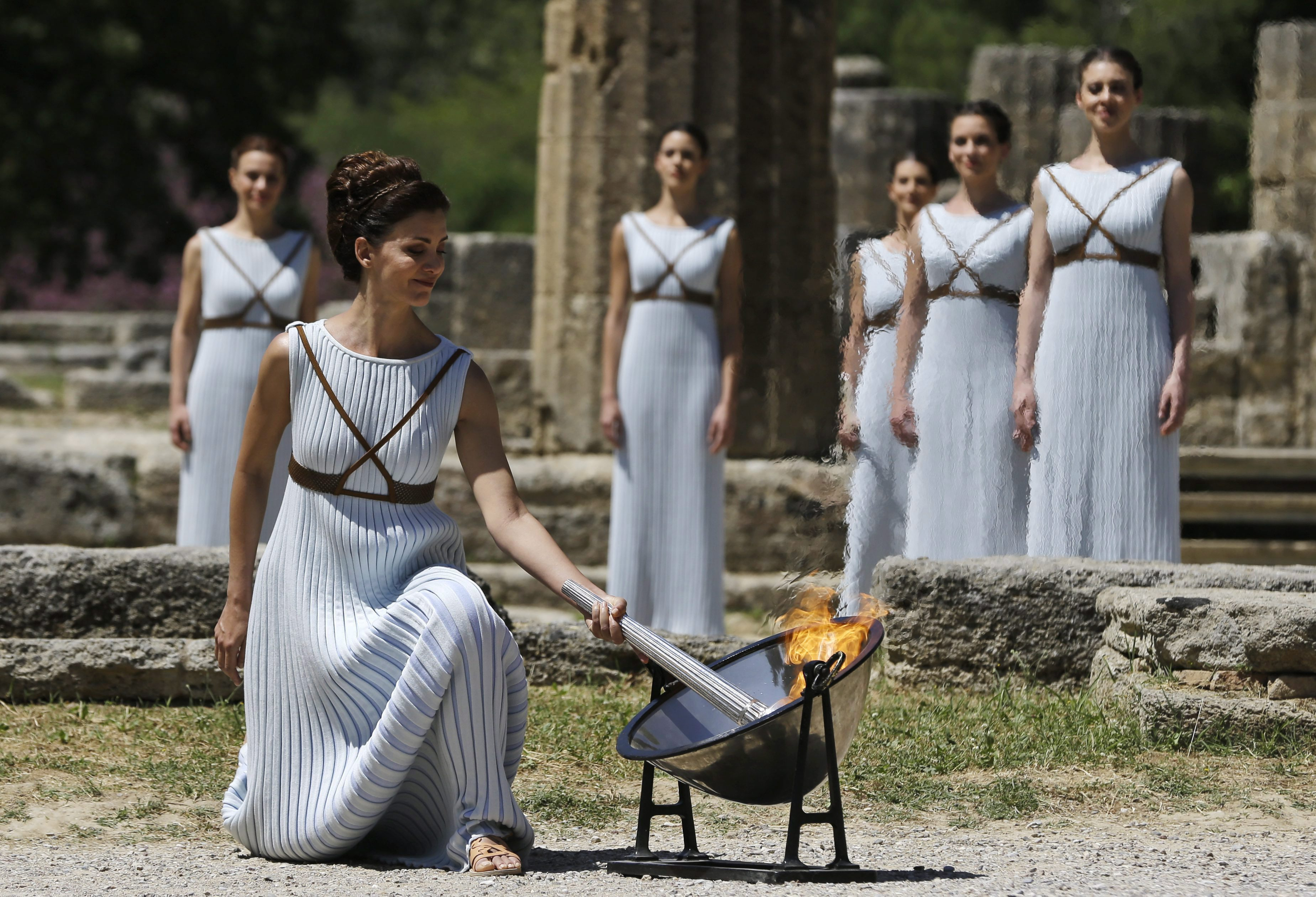A dancer dressed as priestesses lights the Rio Olympic torch with a parabolic mirror