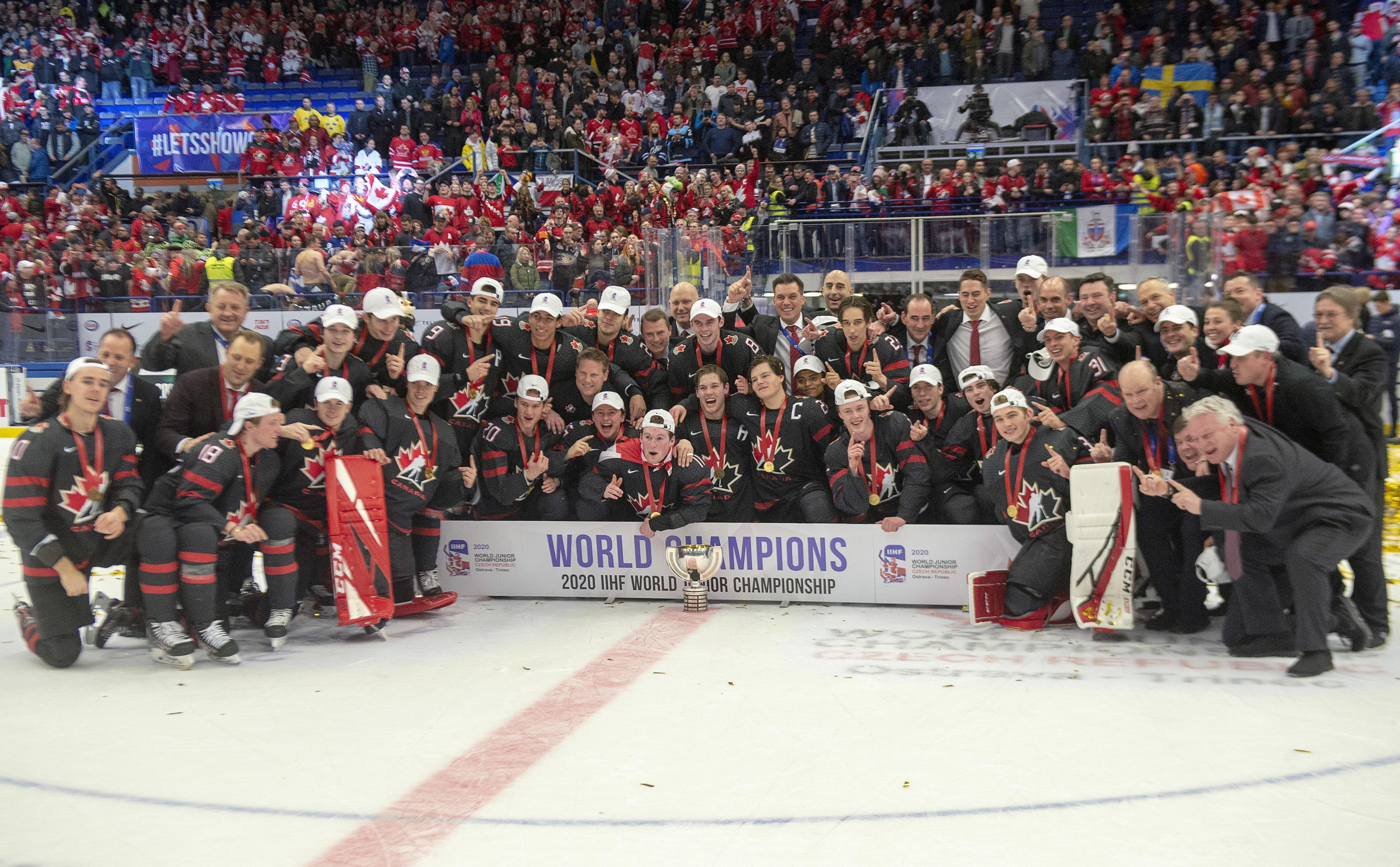 Un groupe de joueurs de hockey pose sur la glace avec la bannière des champions.