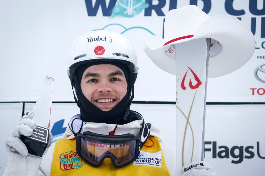 Mikael Kingsbury holds his trophy in his right hand and his skis in his left which have a white cowboy hat on them.