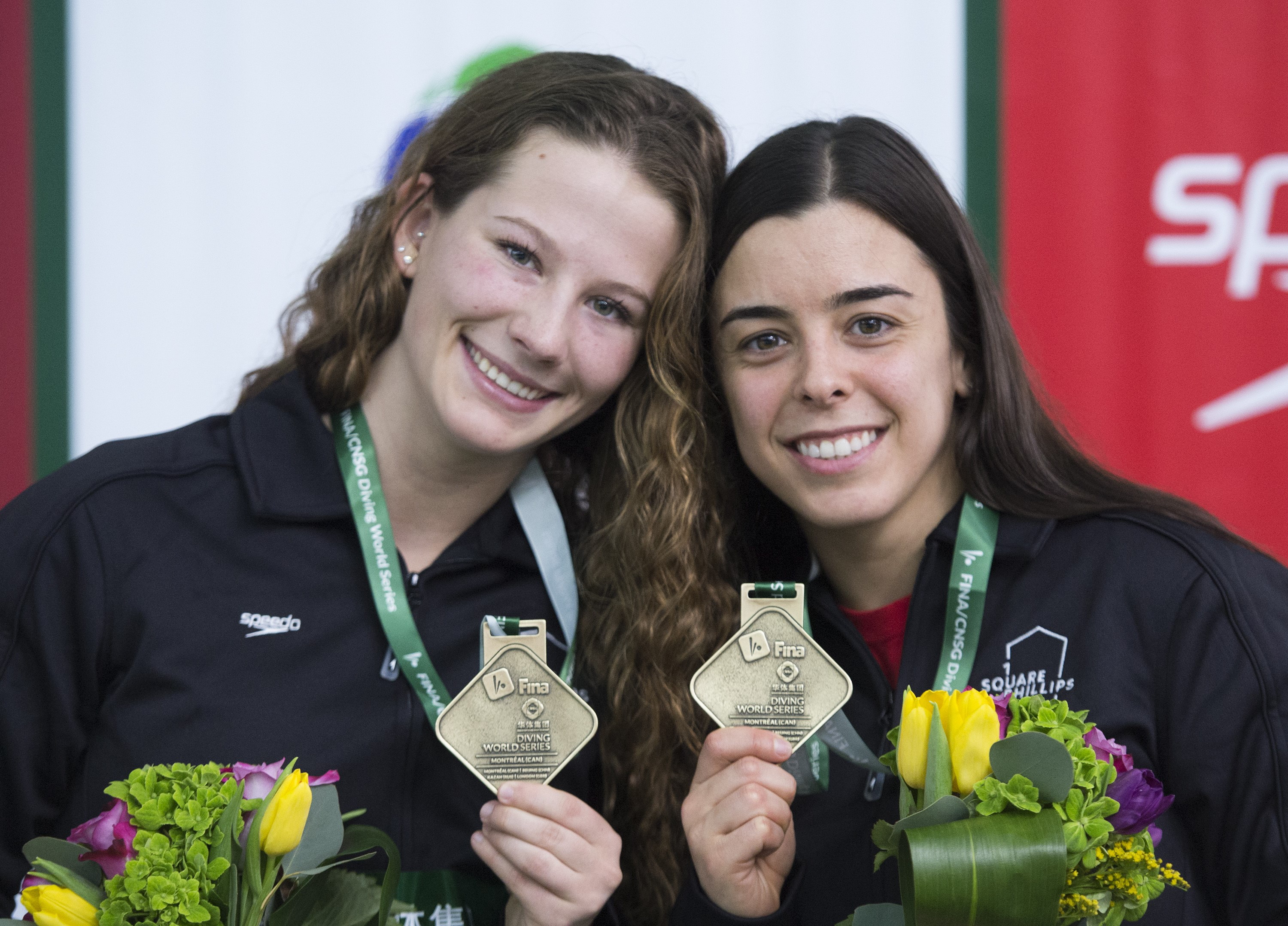 Meaghan Benfeito, right, and Caeli McKay of Canada hold up their gold medals after winning the women's 10-metre platform synchro final.