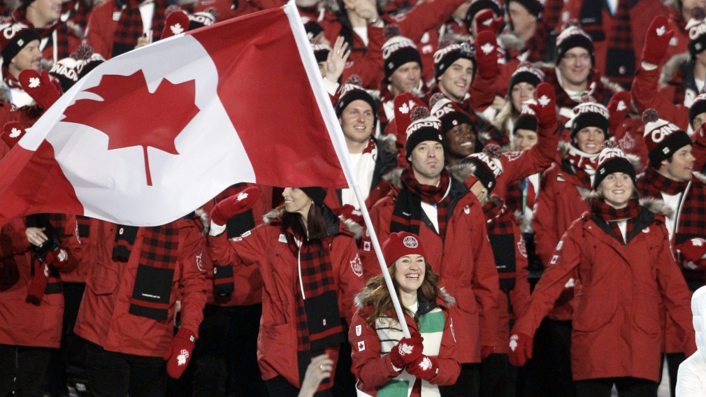 Les athlètes canadiens entrent dans le stade, menés par Clara Hughes