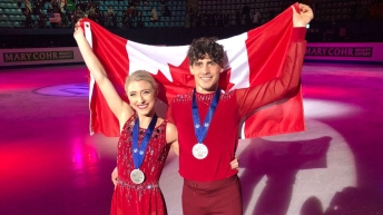 Piper Gilles (left) and Paul Poirier pose for a photo with their medals and the Team Canada flag.