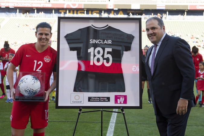 Christine Sinclair is given a commemorative jersey by Victor Montagliani.