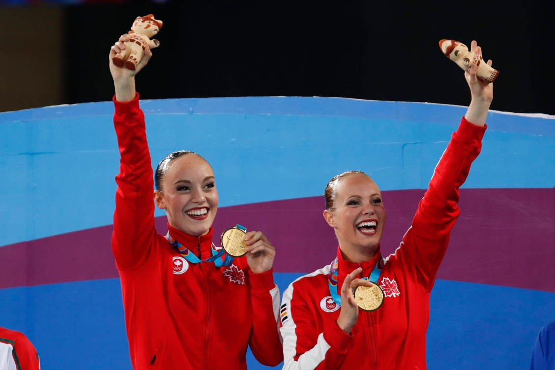 Jacqueline Simoneau, right, and Claudia Holzner, of Canada, celebrates after receiving their gold medals in the artistic swimming duet free routine finals at the Pan American Games in Lima, Peru, Wednesday, July 31, 2019.
