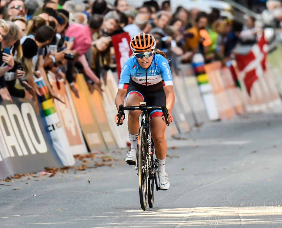 Karol-Ann Canuel cycling at the 2018 UCI World Championships. She is the only cyclist in the shot and is wearing an orange helmet, a blue and white top with black biker shorts that have red and blue detailing.