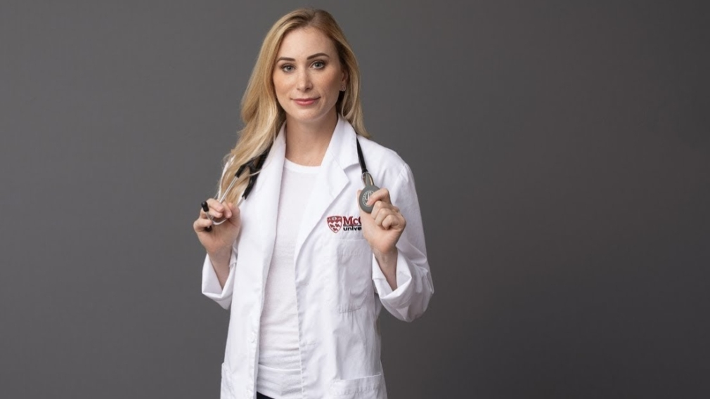 Joannie Rochette holds a stethoscope over her shoulders, posing for a photo in her white doctor's coat.