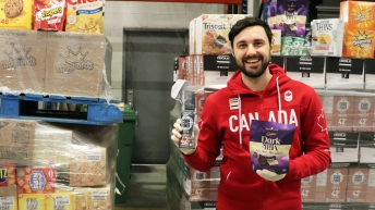 Joseph Polossifakis holds onto a back of Cadbury Dark Milk mini bars in his left hand and a Core Power Elite Drink in the other.