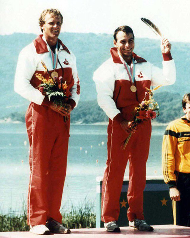 Alwyn Morris holds an eagle feather on the Olympic podium alongside Hugh Fisher