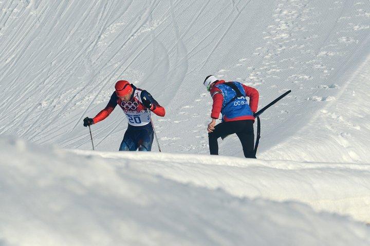 coach helping skiier
