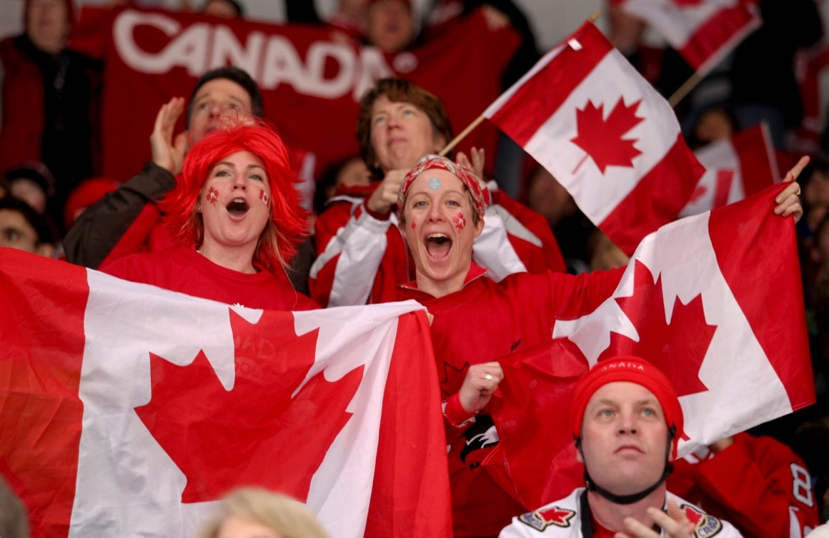 Two fans with Canadian flags cheering