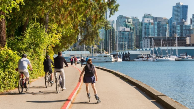 Roller bladers and cyclists on bike path looking out on to the city by the water in Vancouver on a sunny day
