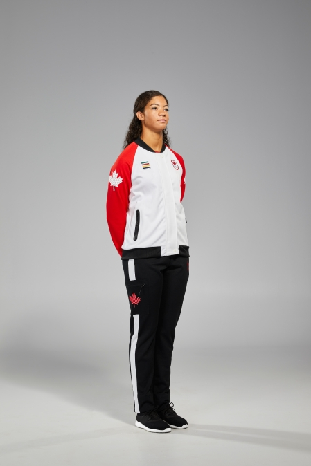Douglas side view with hands in jacket pocket that has red arms white body, and black pants