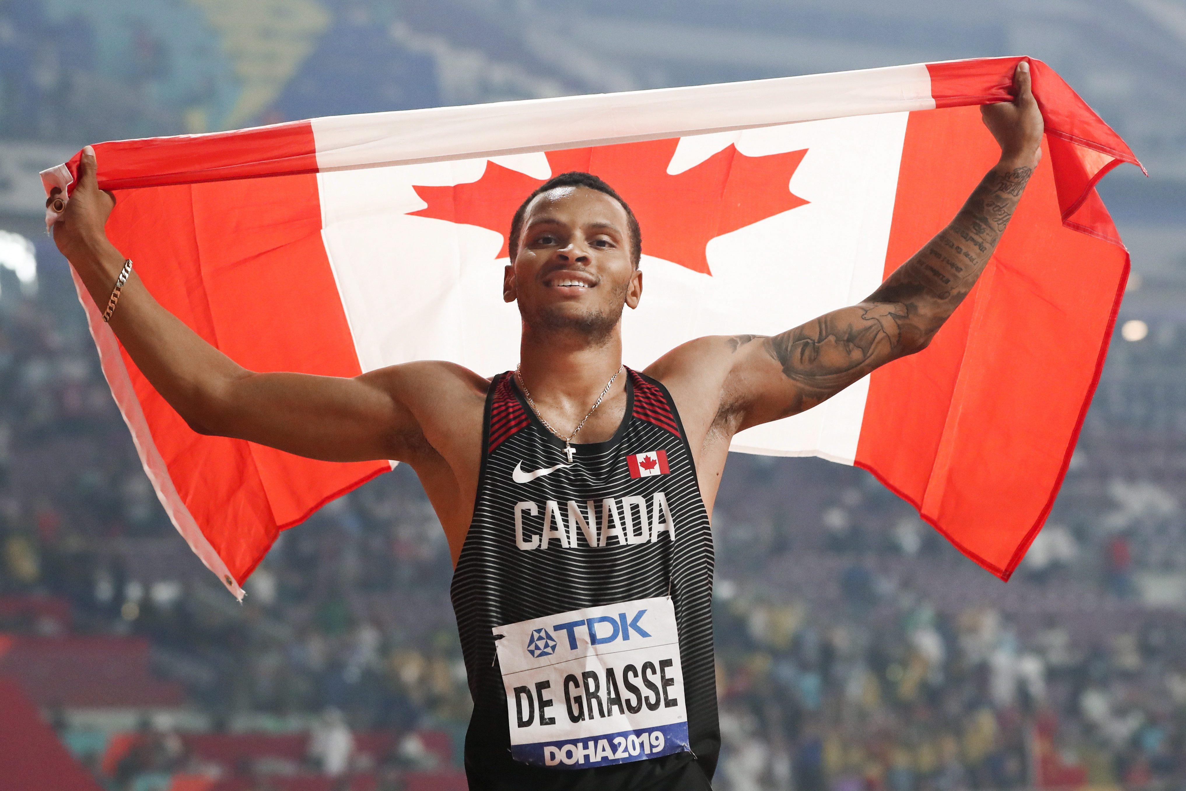 De Grasse holding Canadian flag above head smiling