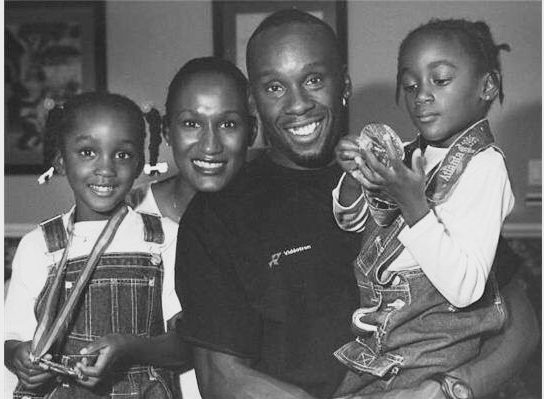 Bruny Surin and his young daughters wearing his medals