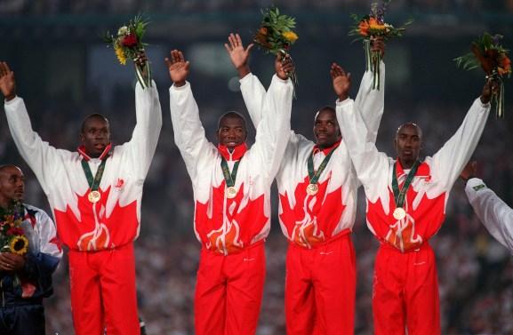 Donovan Bailey, Bruny Surin, Glenroy Gilbert and Robert Esmie raise their hands as they celebrate gold.