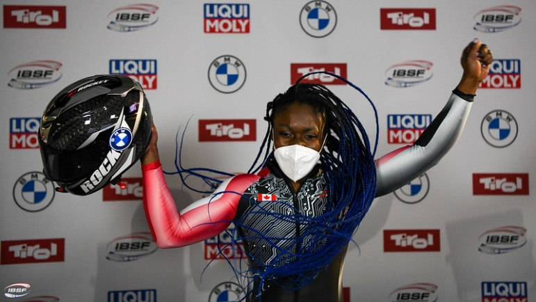Cynthia Appiah raises her hands in the air, holding her helmet in her right hand.