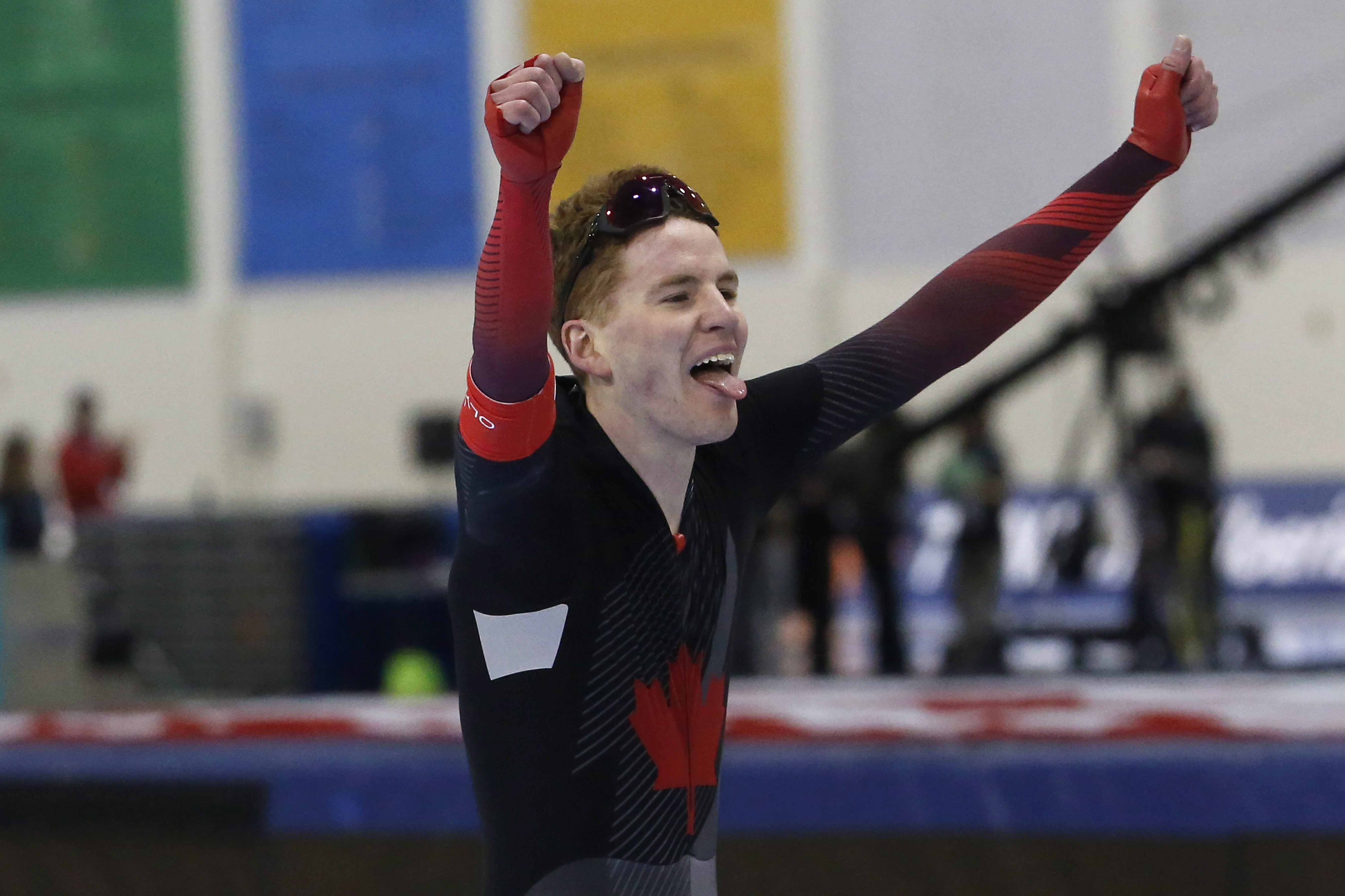 Speed skater holds his arms up in the air in celebration